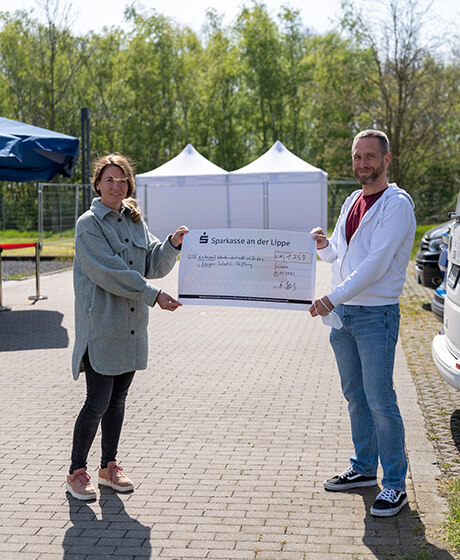 itemis employee Arne hands over a check in the amount of 1758 euros to a representative of the Neven Subotic Foundation